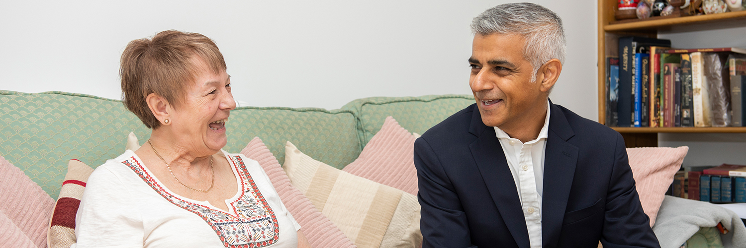 The Mayor in the home of a resident sat on the sofa laughing
